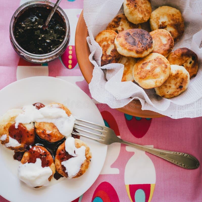 Σπιτικές τηγανίτες τυριών εξοχικών σπιτιών με τη μαρμελάδα και την κρεμώδη σάλτσα στοκ φωτογραφία με δικαίωμα ελεύθερης χρήσης