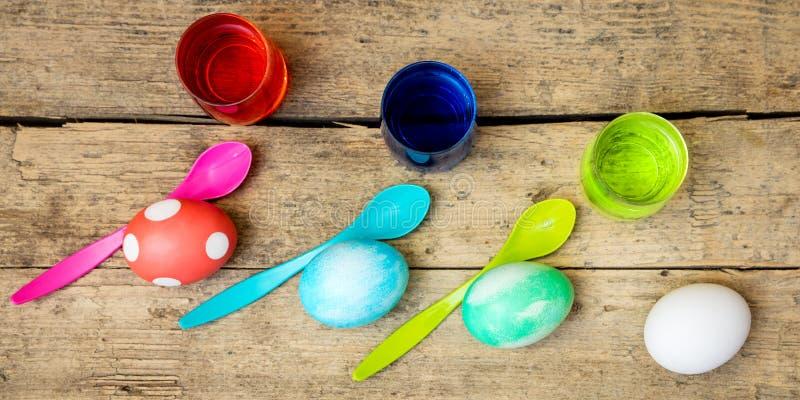 Σπιτικές χρωστικές ουσίες, αυγά, ζωγραφική και κουτάλια αυγών Πάσχας στο ξύλινο TA στοκ φωτογραφίες
