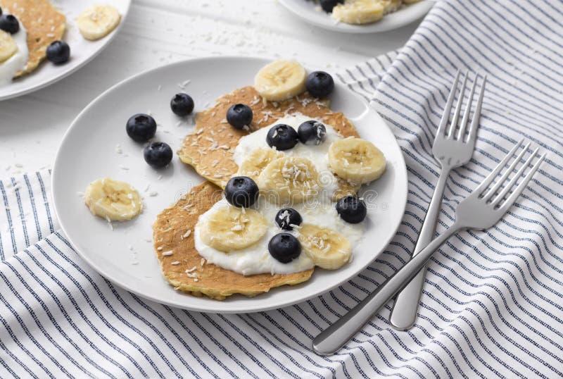 Σπιτικές oatmeal τηγανίτες με το γιαούρτι, το φρέσκες βακκίνιο και την μπανάνα στο άσπρο ξύλινο υπόβαθρο στοκ εικόνες