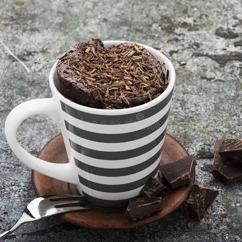 Σπιτική αρωματική κούπα σοκολάτας cupcake σε μια μοντέρνη γκρίζα ριγωτή κούπα σε ένα γκρίζο υπόβαθρο πετρών με τα κομμάτια πικρού στοκ εικόνες