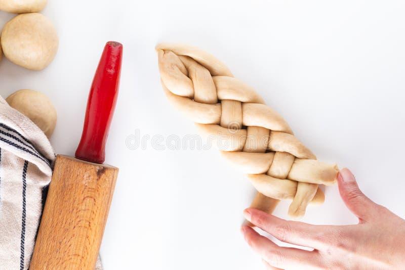 Σπιτική ζύμη πλεξουδών ψωμιού πλεξίματος διαδικασίας έννοιας τροφίμων challah στο άσπρο υπόβαθρο με το διάστημα αντιγράφων στοκ εικόνες