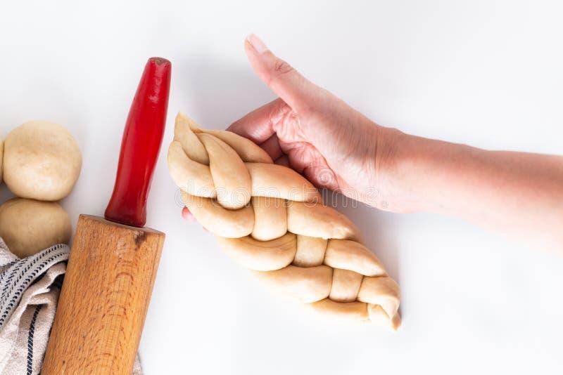 Σπιτική ζύμη πλεξουδών ψωμιού πλεξίματος διαδικασίας έννοιας τροφίμων challah στο άσπρο υπόβαθρο με το διάστημα αντιγράφων στοκ φωτογραφία
