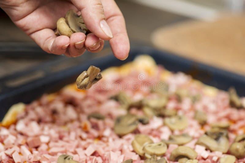 σπιτική πίτσα Αρχιμάγειρας που βάζει τα μανιτάρια στην πίτσα στο εστιατόριο πιτσών Κάνοντας διαδικασία πιτσών στοκ φωτογραφίες