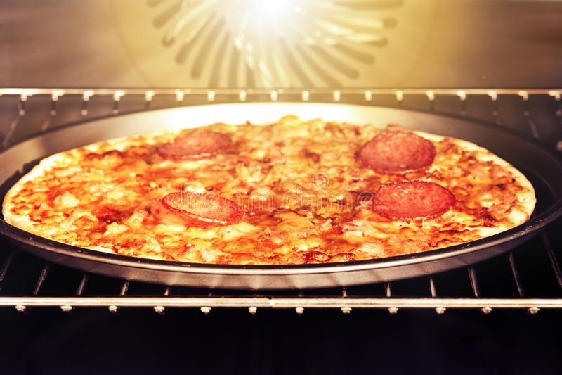 Σπιτική πίτσα με το τυρί και σαλάμι σε έναν ηλεκτρικό φούρνο στοκ φωτογραφία