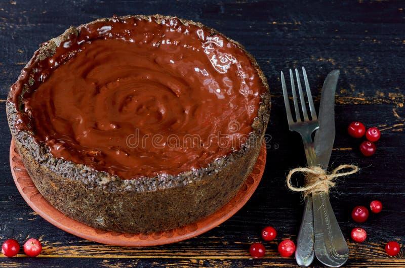 Σπιτική σοκολάτα ξινή που διακοσμεί με το το βακκίνιο, το εκλεκτής ποιότητας μαχαίρι και το δίκρανο στο σκοτεινό ξύλινο υπόβαθρο  στοκ εικόνες