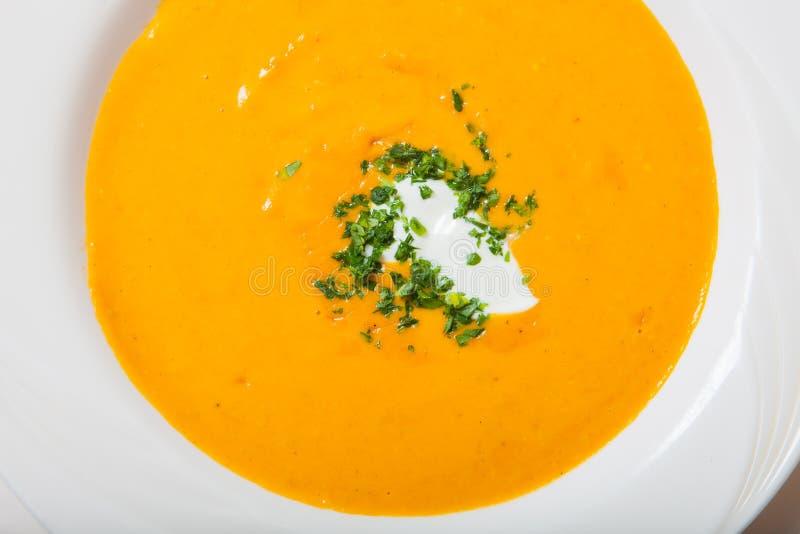 Σπιτική σούπα κολοκύθας με την κρέμα με τα καρυκεύματα στο άσπρο πιάτο στοκ φωτογραφίες