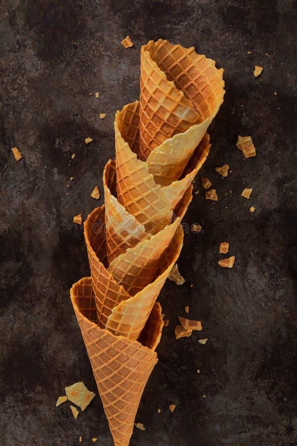 Σπιτικοί συσσωρευμένοι κενοί κορνέτες ή κώνοι βαφλών παγωτού στο σκοτεινό υπόβαθρο Εκλεκτική εστίαση Το ελάχιστο επίπεδο βάζει τη στοκ εικόνες