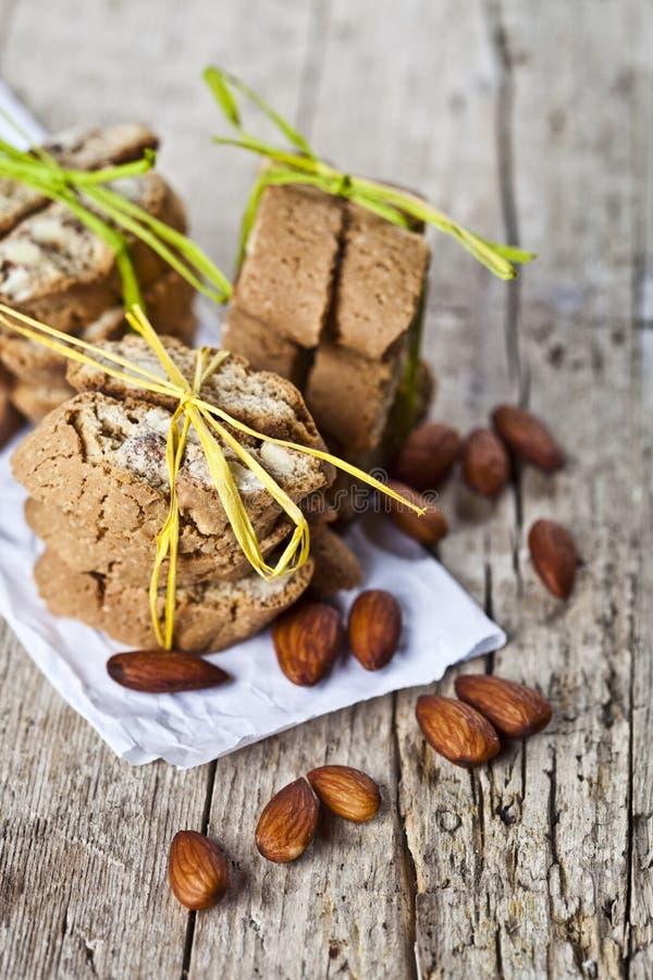 Σπιτικοί φρέσκοι ιταλικοί σωροί cantuccini μπισκότων και οργανικοί σπόροι αμυγδάλων στη Λευκή Βίβλο για το ructic ξύλινο επιτραπέ στοκ εικόνα με δικαίωμα ελεύθερης χρήσης