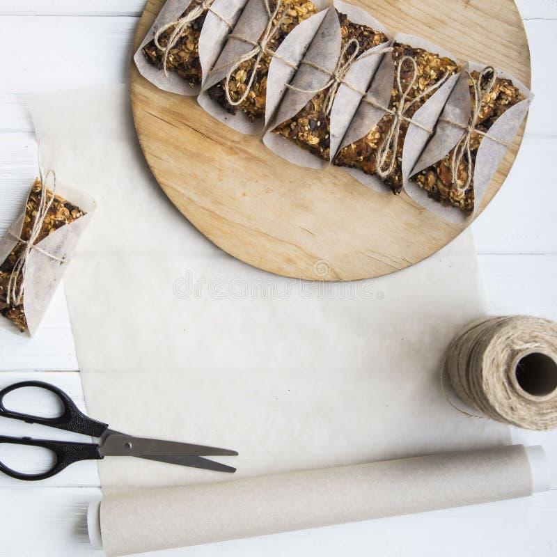 Σπιτικοί φραγμοί muesli με ξηρό - φρούτα, καρύδια και oatmeal Σχεδιάγραμμα υποβάθρου με το διάστημα ελεύθερων κειμένων Επίπεδος β στοκ εικόνα