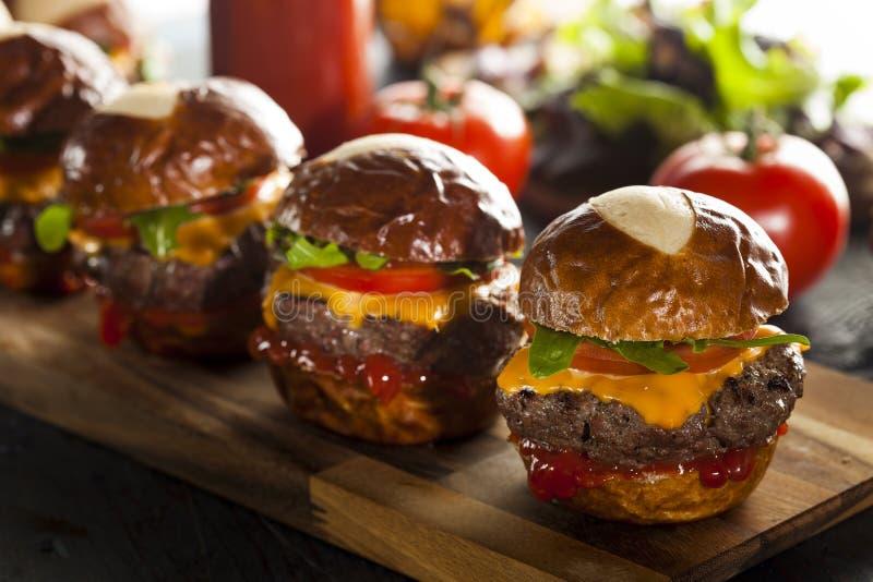 Σπιτικοί Cheeseburger ολισθαίνοντες ρυθμιστές με το μαρούλι στοκ εικόνες