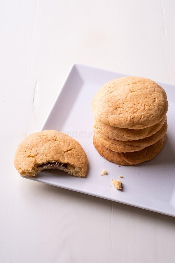 Σπιτικός σωρός των μπισκότων σοκολάτας κουλουρακιών με ένα δαγκωμένο μπισκότο στον άσπρο ξύλινο πίνακα πιάτων στοκ φωτογραφία με δικαίωμα ελεύθερης χρήσης