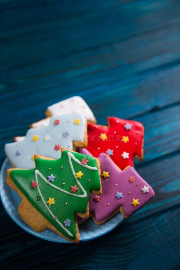 Σπιτικό βερνικωμένο μελόψωμο τέσσερα με μορφή χριστουγεννιάτικου δέντρου που διακοσμείται με τα αστέρια στο πιάτο στον ξύλινο πίν στοκ εικόνα