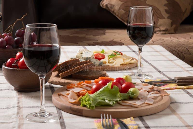 Σπιτικό γεύμα με το ψωμί, τις ντομάτες, το τυρί, το ζαμπόν και το κρασί στοκ εικόνα