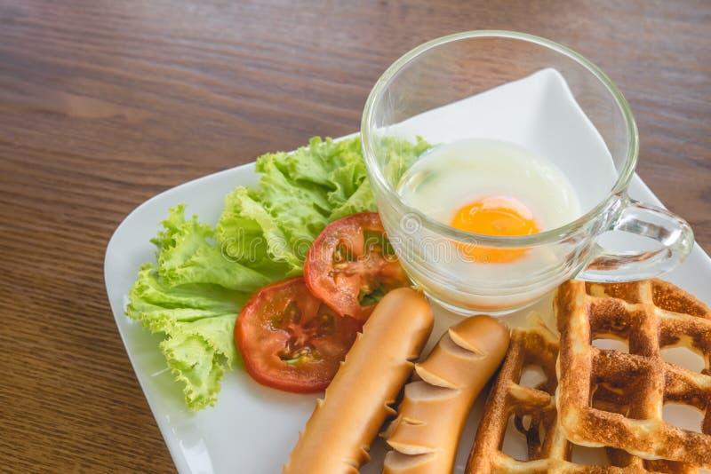 Σπιτικό εύγευστο αμερικανικό πρόγευμα με το μαλακός-βρασμένο αυγό, βάφλες, λουκάνικο, ντομάτα, μαρούλι στο άσπρο πιάτο στον ξύλιν στοκ φωτογραφία με δικαίωμα ελεύθερης χρήσης