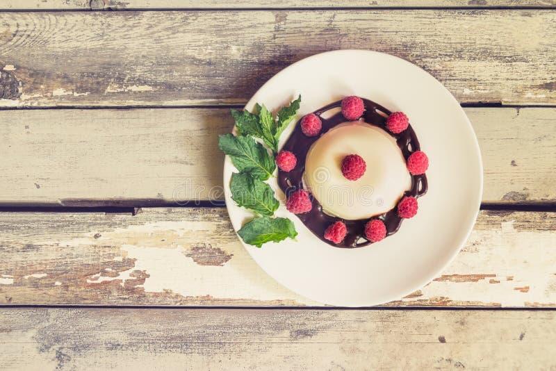 Σπιτικό ιταλικό cotta panna επιδορπίων με το σιρόπι σμέουρων και σοκολάτας στοκ φωτογραφία