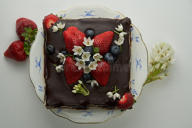 Σπιτικό κέικ σοκολάτας που διακοσμείται με τις φράουλες και τα εδώδιμα λουλούδια στοκ εικόνες
