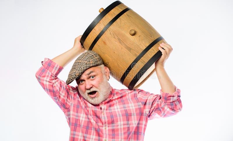 Σπιτικό κρασί Ο γενειοφόρος πρεσβύτερος ατόμων φέρνει το ξύλινο βαρέλι για το άσπρο υπόβαθρο κρασιού Παραγωγή της οικογενειακής π στοκ φωτογραφία με δικαίωμα ελεύθερης χρήσης