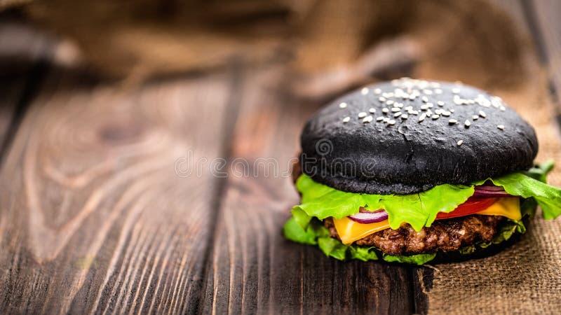 Σπιτικό μαύρο Burger με το τυρί Cheeseburger με το μαύρο κουλούρι ο στοκ εικόνα