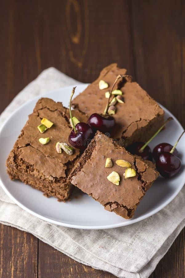 Σπιτικό σκοτεινό κάλυμμα κέικ Brownies σοκολάτας με τα φυστίκια και κεράσι στο άσπρο πιάτο ξύλινο επιτραπέζιο κάθετο εύγευστο σε  στοκ εικόνες