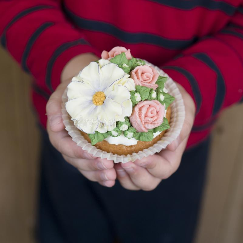 Σπιτικό σφουγγάρι cupcakes με τα λουλούδια buttercream που παγώνουν Το αγόρι κρατά διακοσμημένος cupcake Γλυκό δώρο στο mom στοκ εικόνες με δικαίωμα ελεύθερης χρήσης