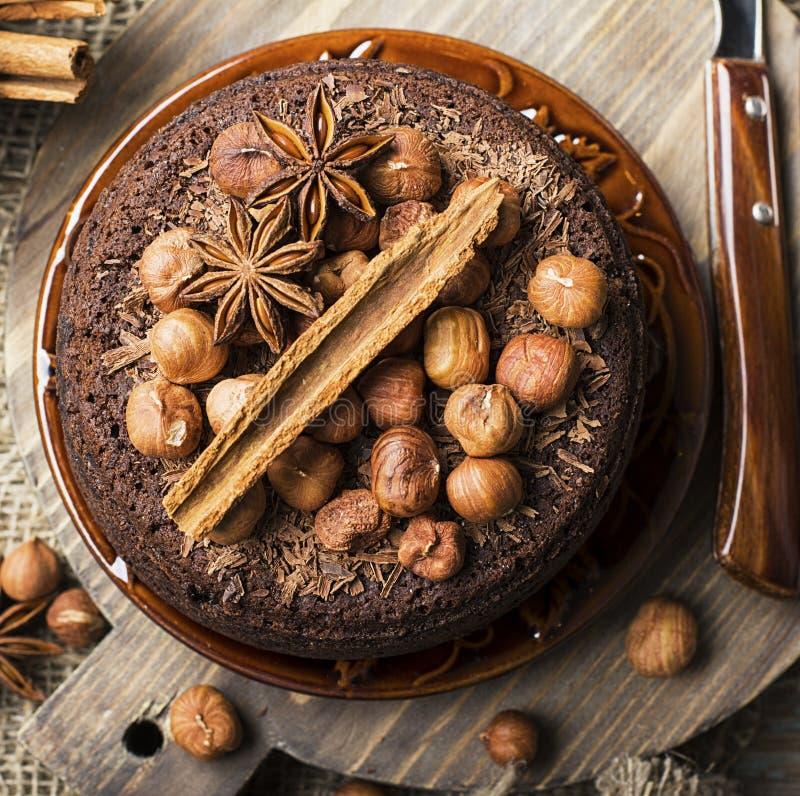 Σπιτικό τρελλό κέικ σοκολάτας με τα τσιπ σοκολάτας, τα φουντούκια καρυδιών, την κανέλα και τα καρυκεύματα για ένα άνετο κόμμα τσα στοκ φωτογραφίες