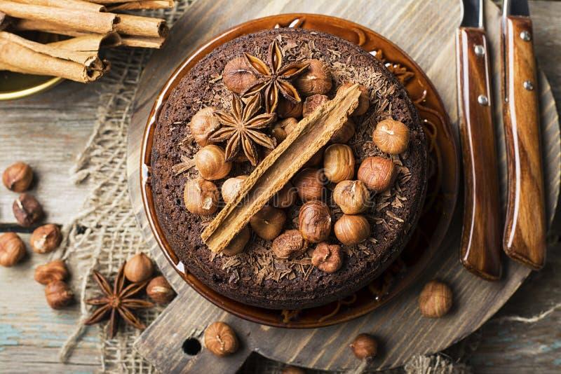 Σπιτικό τρελλό κέικ σοκολάτας με τα τσιπ σοκολάτας, τα φουντούκια καρυδιών, την κανέλα και τα καρυκεύματα για ένα άνετο κόμμα τσα στοκ εικόνες με δικαίωμα ελεύθερης χρήσης