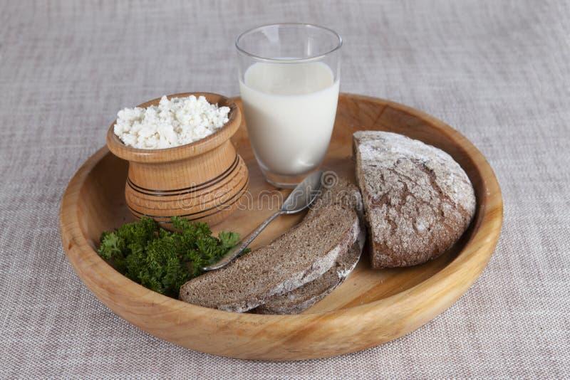 Σπιτικό τυρί, ένα ποτήρι του γάλακτος, καφετί ψωμί σε έναν ξύλινο δίσκο στοκ φωτογραφία με δικαίωμα ελεύθερης χρήσης
