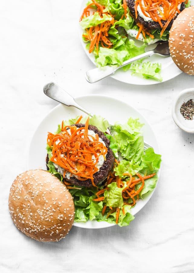 Σπιτικό burger βόειου κρέατος με τα πικάντικα μαριναρισμένα καρότα και την πράσινη σαλάτα - εύγευστο πρόχειρο φαγητό, brunch, tap στοκ εικόνες