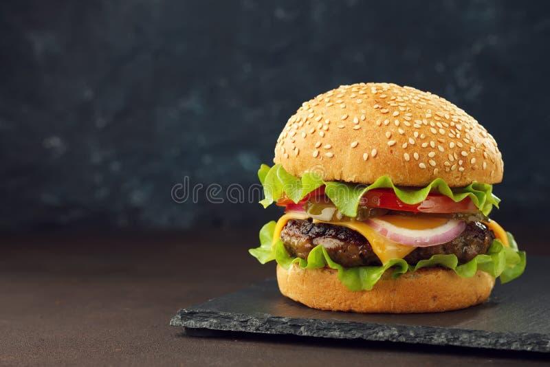 Σπιτικό burger με cutlet βόειου κρέατος, το τυρί Cheddar, το μαρούλι και τα λαχανικά στην πλάκα επιβιβάζονται στοκ εικόνα