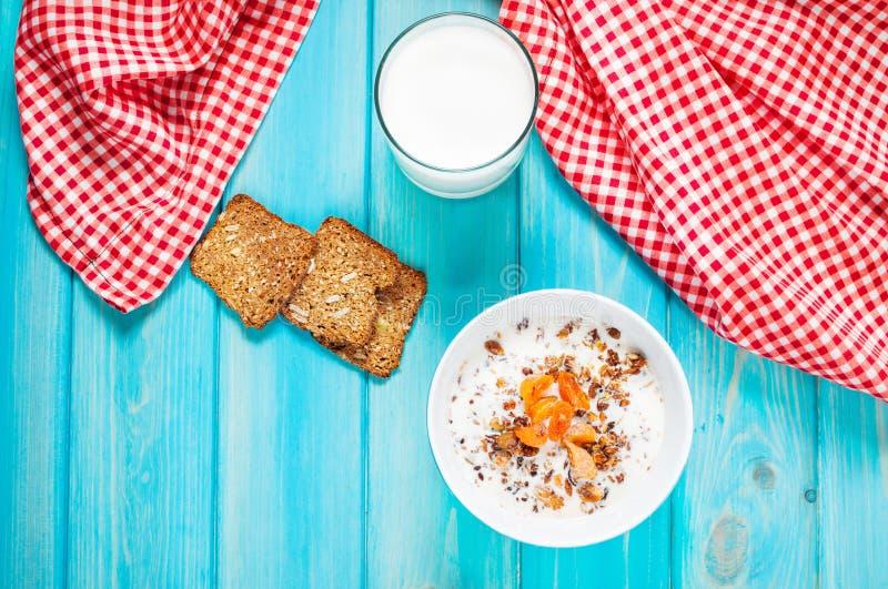 Σπιτικό granola με το γάλα για το πρόγευμα στο μπλε ξύλινο υπόβαθρο στοκ φωτογραφία με δικαίωμα ελεύθερης χρήσης