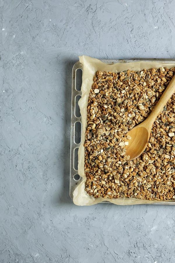 Σπιτικό granola σε ένα φύλλο ψησίματος σε ένα κατασκευασμένο συγκεκριμένο υπόβαθρο με ένα ξύλινο κουτάλι Τοπ όψη Επίπεδος βάλτε Τ στοκ εικόνες με δικαίωμα ελεύθερης χρήσης