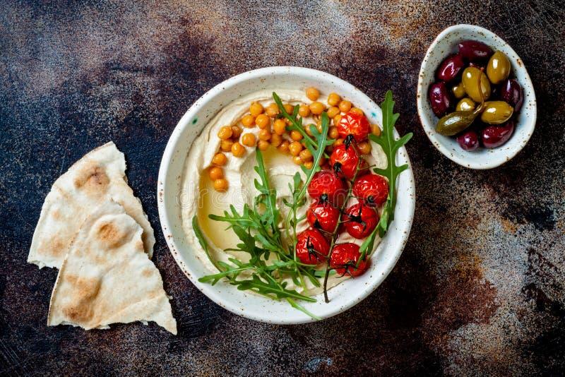 Σπιτικό hummus με τις ψημένες ντομάτες και τις ελιές κερασιών Μεσο-Ανατολική παραδοσιακή και αυθεντική αραβική κουζίνα στοκ εικόνες