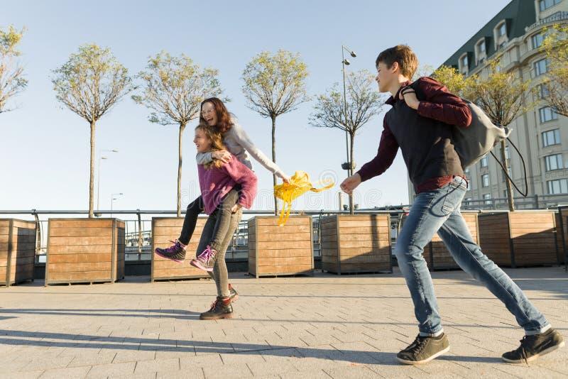 Σπουδαστές εφήβων φίλων με τα σχολικά σακίδια πλάτης, που έχουν τη διασκέδαση στον τρόπο από το σχολείο στοκ φωτογραφία