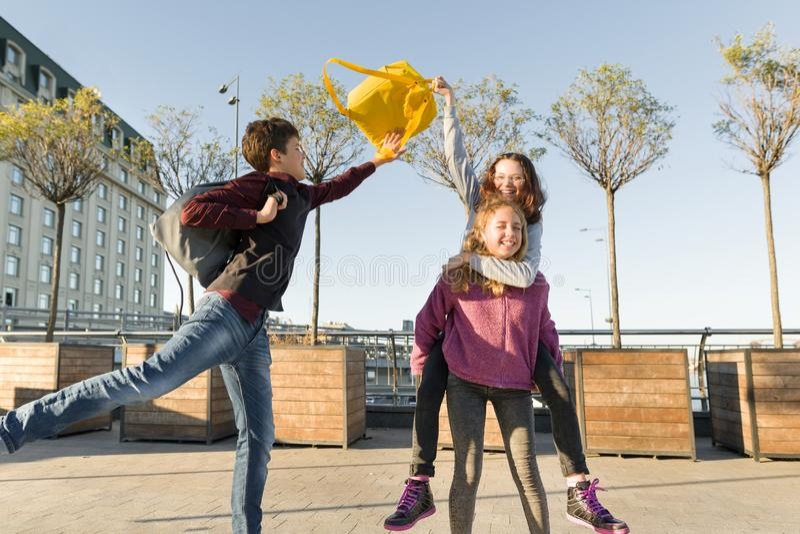 Σπουδαστές εφήβων φίλων με τα σχολικά σακίδια πλάτης, που έχουν τη διασκέδαση στον τρόπο από το σχολείο στοκ φωτογραφία με δικαίωμα ελεύθερης χρήσης