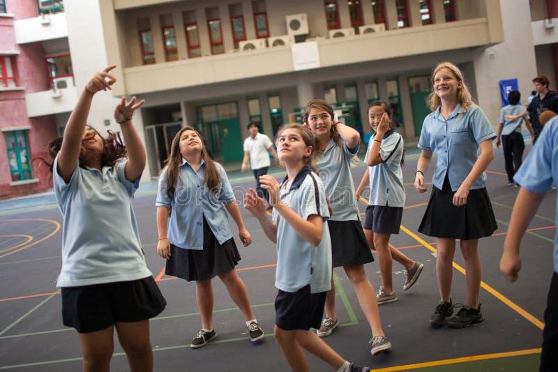 Σπουδαστές με ομοιόμορφο έχοντας την παίζοντας καλαθοσφαίριση διασκέδασης στοκ φωτογραφία με δικαίωμα ελεύθερης χρήσης