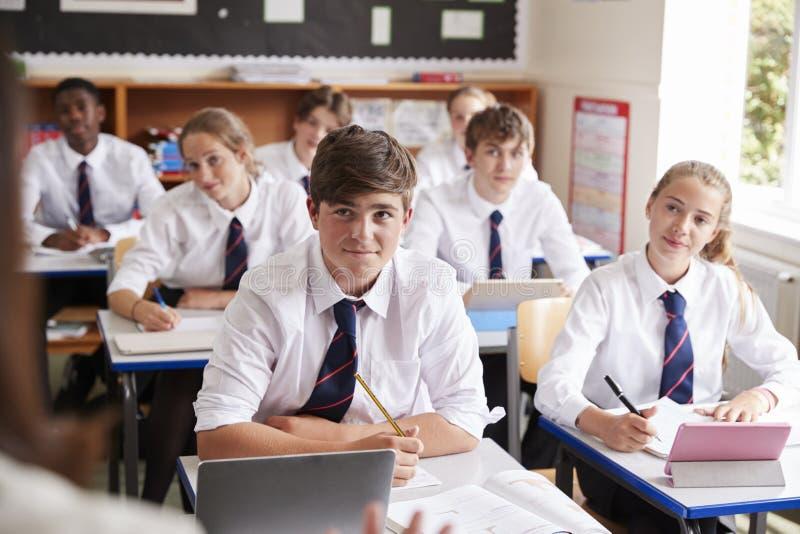 Σπουδαστές που ακούνε το θηλυκό δάσκαλο στην τάξη στοκ εικόνες