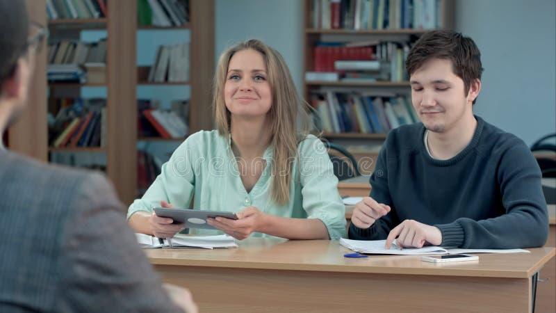 Σπουδαστές που δακτυλογραφούν στον υπολογιστή ταμπλετών σε μια τάξη στοκ φωτογραφία