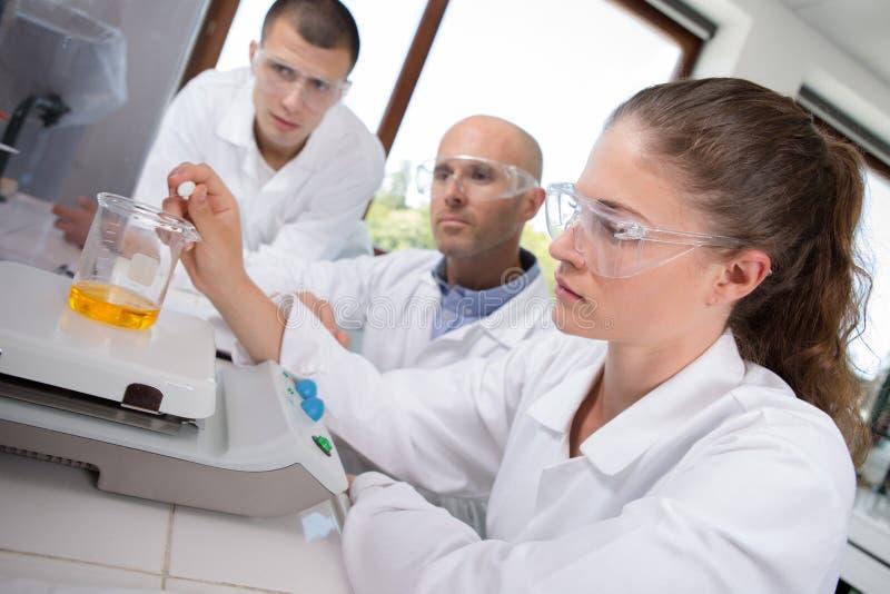 Σπουδαστές που κάνουν τα πειράματα με το δάσκαλο στο εργαστήριο στοκ φωτογραφία