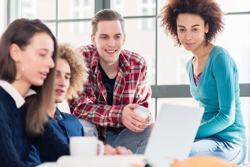 Σπουδαστές που προσέχουν μαζί ένα αστείο σε απευθείας σύνδεση βίντεο σε ένα lap-top κατά τη διάρκεια του σπασίματος στοκ εικόνες με δικαίωμα ελεύθερης χρήσης