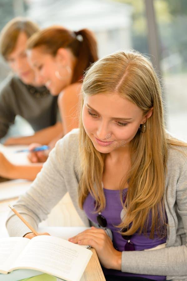 Σπουδαστής γυμνασίου που παίρνει τις σημειώσεις στη μελέτη βιβλιοθηκών στοκ φωτογραφία