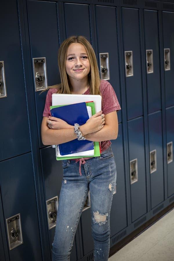 Σπουδαστής Γυμνασίου που υπερασπίζεται το ντουλάπι της σε έναν σχολικό διάδρομο στοκ φωτογραφία