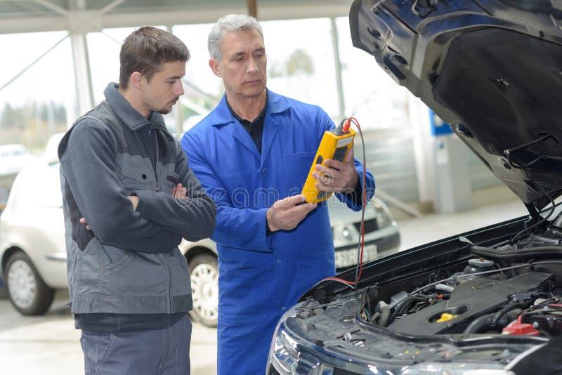 Σπουδαστής με τον εκπαιδευτικό που επισκευάζει το αυτοκίνητο κατά τη διάρκεια της μαθητείας στοκ εικόνα