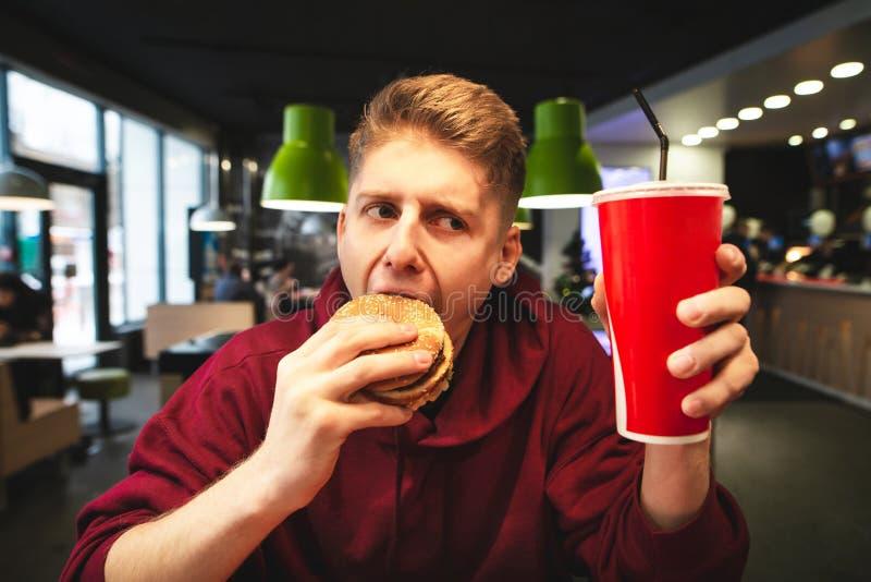 Σπουδαστής που τρώει burger στα εστιατόρια γρήγορου φαγητού, που κρατά ένα ποτήρι των ποτών στα χέρια του και που δαγκώνει ορεκτι στοκ εικόνες
