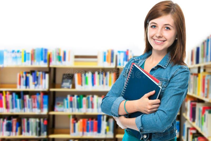 Σπουδαστής στη βιβλιοθήκη πανεπιστημιουπόλεων στοκ φωτογραφία