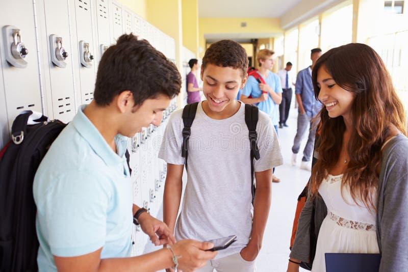 Σπουδαστές γυμνασίου από τα ντουλάπια που εξετάζουν το κινητό τηλέφωνο στοκ φωτογραφία με δικαίωμα ελεύθερης χρήσης