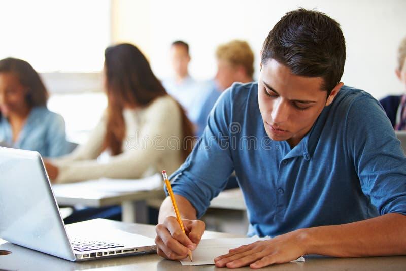 Σπουδαστές γυμνασίου που δίνουν την εξέταση στην τάξη στοκ φωτογραφία
