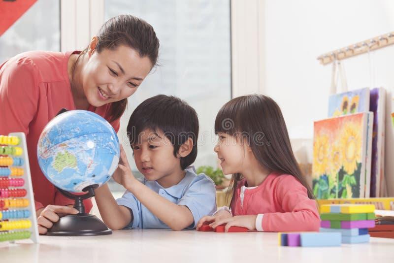 Σπουδαστές και δάσκαλος που εξετάζουν τη σφαίρα στοκ εικόνες με δικαίωμα ελεύθερης χρήσης