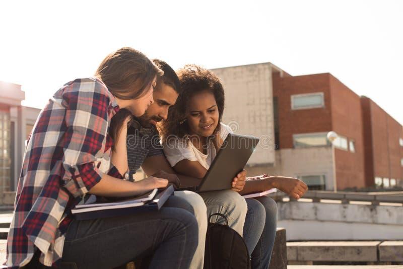 Σπουδαστές με το lap-top στην πανεπιστημιούπολη στοκ φωτογραφία
