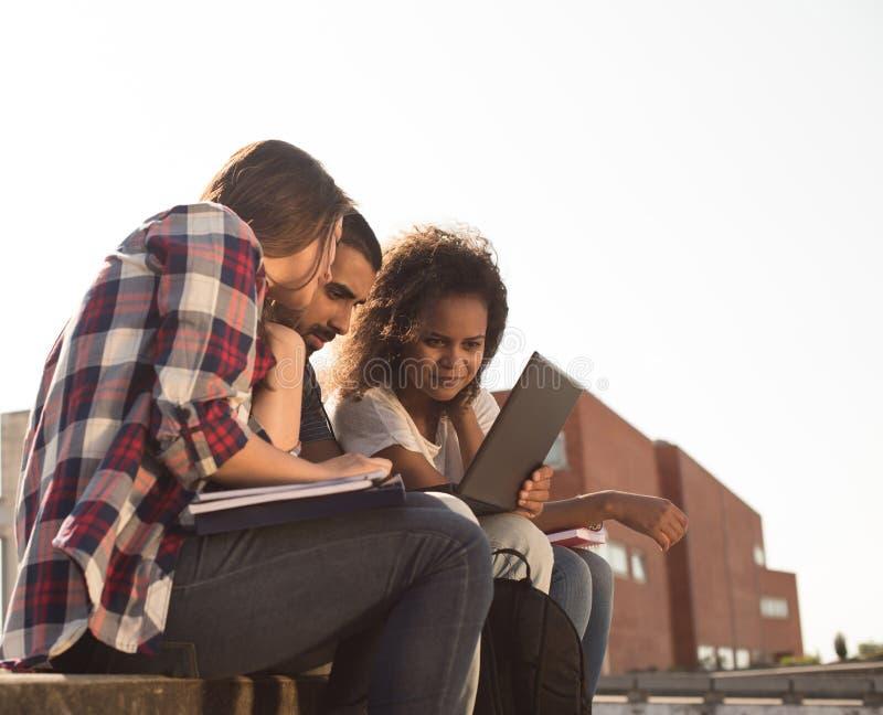 Σπουδαστές με το lap-top στην πανεπιστημιούπολη στοκ φωτογραφία με δικαίωμα ελεύθερης χρήσης
