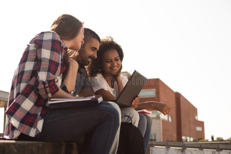 Σπουδαστές με το lap-top στην πανεπιστημιούπολη στοκ εικόνες